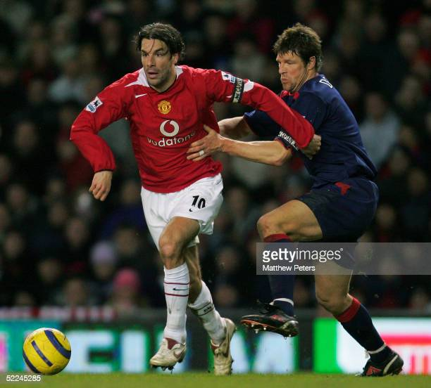 Ruud van Nistelrooy of Manchester United clashes with Arjan De Zeeuw of Portsmouth during the Barclays Premiership match between Manchester United...