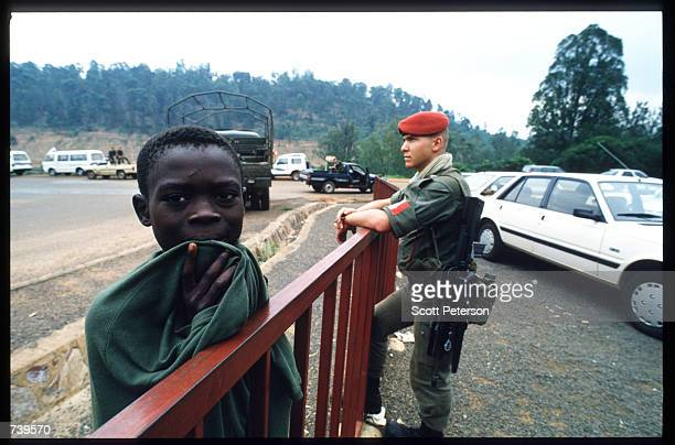 Rwandan boy stands near a watchful soldier as civilians evacuate April 11 1994 in Kigali Rwanda The majority of French and Belgian nationals living...