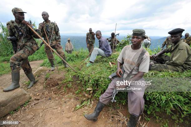 Rwandan Defense Forces troops pass former members of the renegade militia PARECO who now form part of the Congolese military as they walk through...