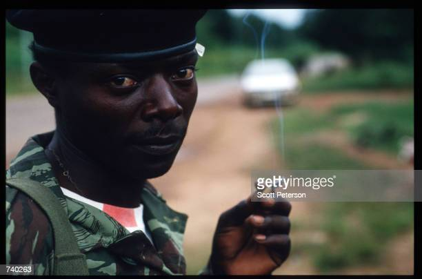 Rwandan Patriotic Front soldier smokes May 26 1994 as he waits to march into Kigali Rwanda Refugees flee the genocide of more than 800000 Tutsis and...