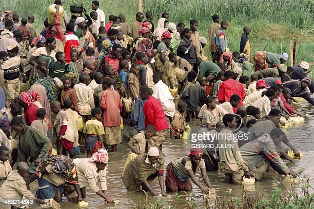 Rwandan refgugees provide themselves with water in a polluted lake near the Tanzanian refugee camp of Benako on May 05 1994 Hundreds of thousands of...