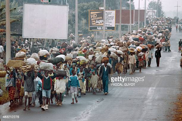 Rwandan refugees cross the Zairean border at Goma to flee the Rwandan Patriotic Front troops advance on the northwestern town of Gisenyi on July 19...