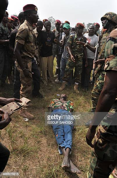 A Rwandan soldier of the African Unionled MISCA mission tries to prevent members of the Central African Armed Forces from lynching a man suspected of...
