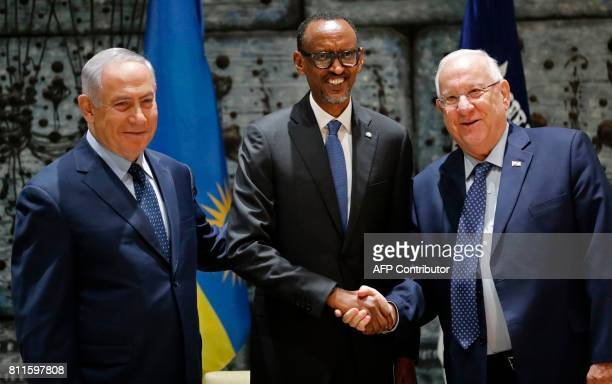Rwanda's President Paul Kagame shakes hands with Israeli President Reuven Rivlin and Israeli Prime Minister Benjamin Netanyahu during their meeting...