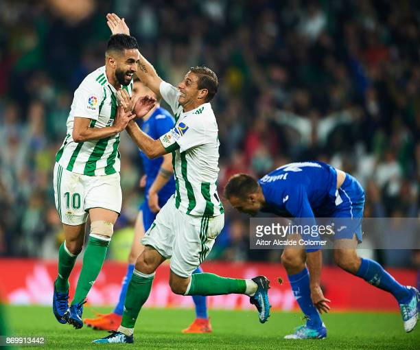 Ryad Boudebouz of Real Betis Balompie celebrates after scoring the seconf goal for Real Betis Balompie with his team mate Joaquin Sanchez of Real...