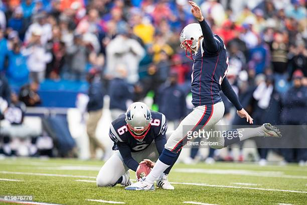 Ryan Allen holds for Stephen Gostkowski of the New England Patriots as he kicks a point after try during the first half against the Buffalo Bills on...