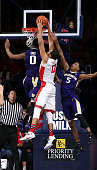 Ryan Anderson of the Arizona Wildcats dunks over Marquese Chriss of the Washington Huskies and Dejounte Murray during the second half of the college...