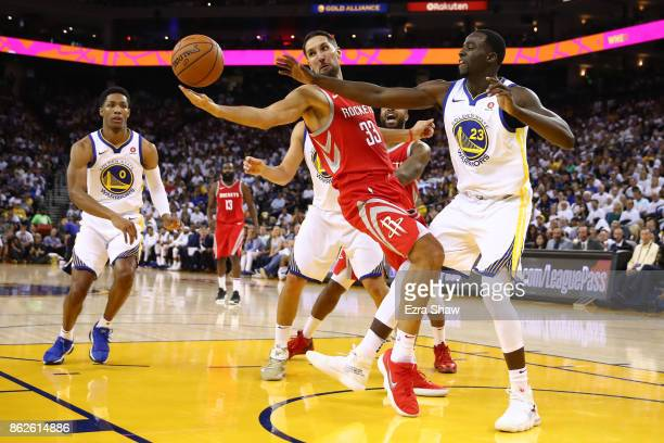 Ryan Anderson of the Houston Rockets and Draymond Green of the Golden State Warriors go for the ball during their NBA game at ORACLE Arena on October...