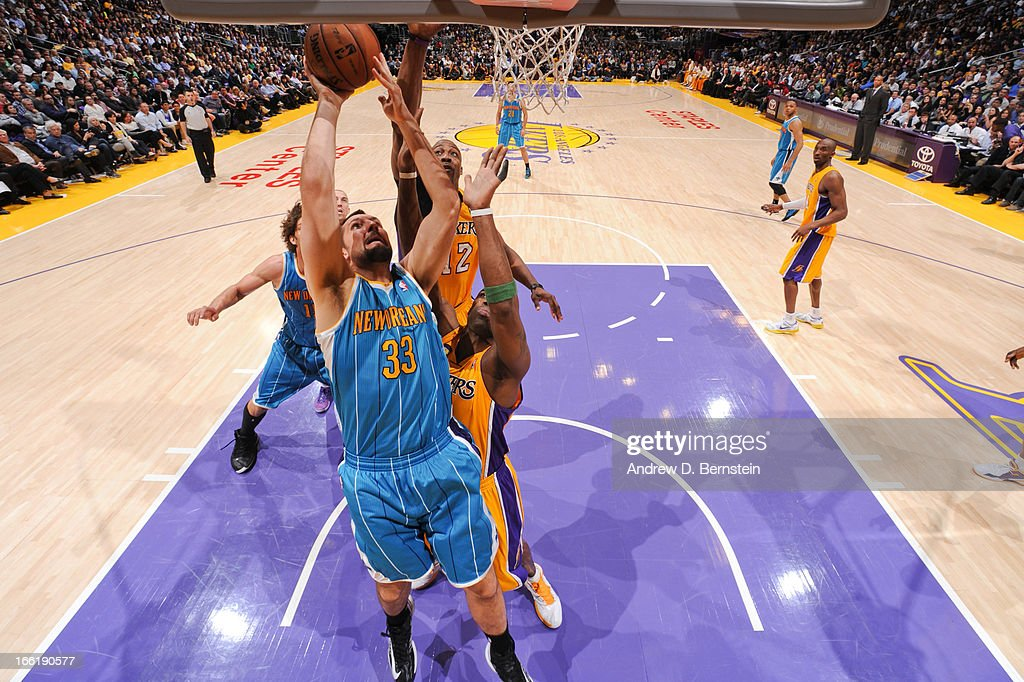 Ryan Anderson #33 of the New Orleans Hornets attempts a layup against Dwight Howard #12 and Antawn Jamison #4 of the Los Angeles Lakers at Staples Center on April 9, 2013 in Los Angeles, California.