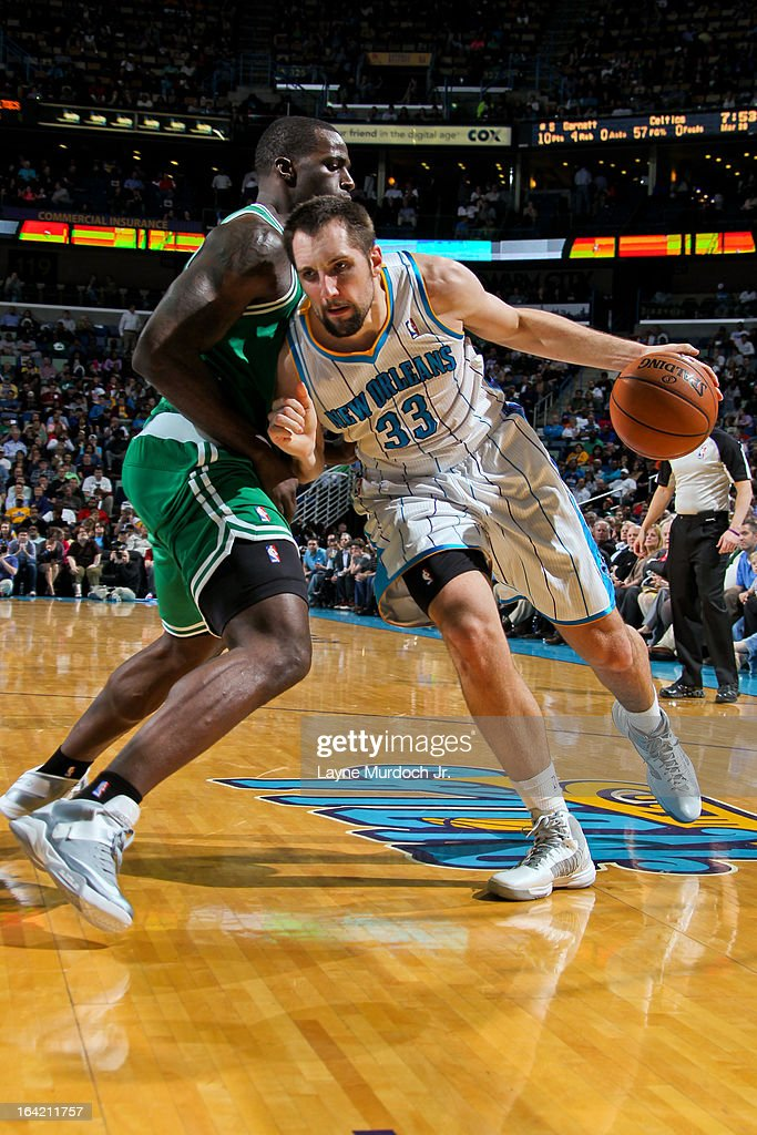 Ryan Anderson #33 of the New Orleans Hornets drives against Brandon Bass #30 of the Boston Celtics on March 20, 2013 at the New Orleans Arena in New Orleans, Louisiana.