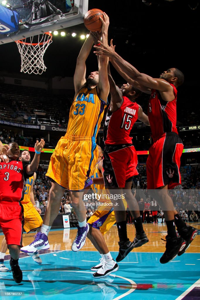 Ryan Anderson #33 of the New Orleans Hornets grabs a rebound against <a gi-track='captionPersonalityLinkClicked' href=/galleries/search?phrase=Amir+Johnson&family=editorial&specificpeople=556786 ng-click='$event.stopPropagation()'>Amir Johnson</a> #15 of the Toronto Raptors on December 28, 2012 at the New Orleans Arena in New Orleans, Louisiana.