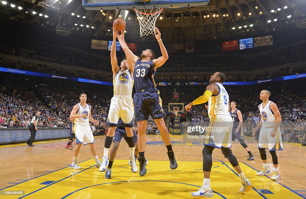 Ryan Anderson #33 of the New Orleans Pelicans rebounds against Andrew Bogut #12 of the Golden State Warriors on December 17, 2013 at Oracle Arena in Oakland, California.