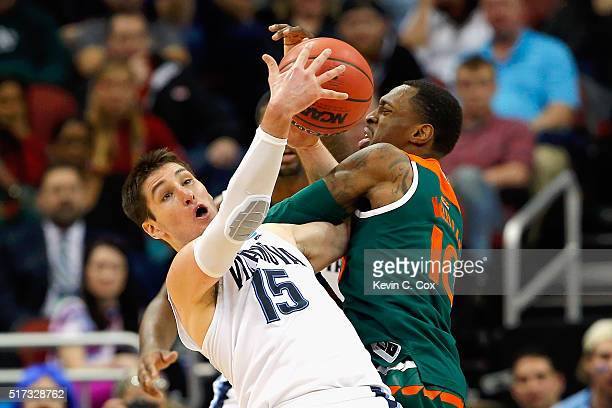 Ryan Arcidiacono of the Villanova Wildcats and Sheldon McClellan of the Miami Hurricanes battle for the ball in the first half of their game during...