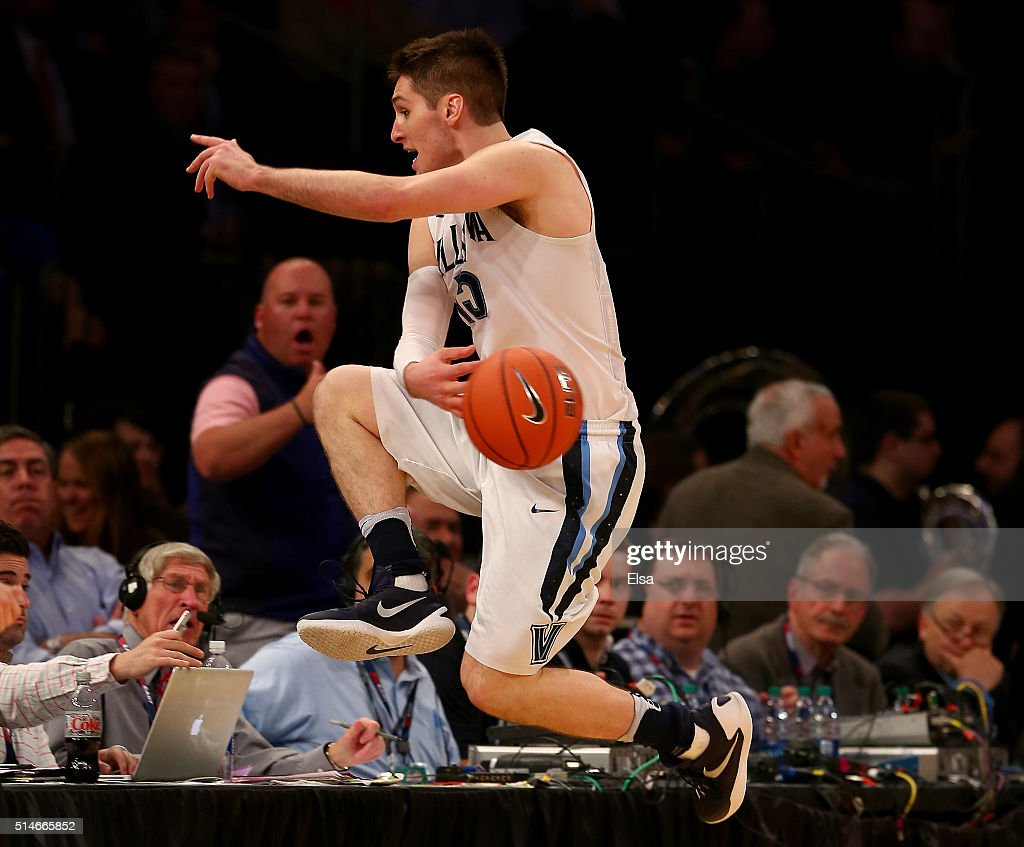 Ryan Arcidiacono of the Villanova Wildcats leaps into the front row as he keep the ball in play in the second half against the Georgetown Hoyas...
