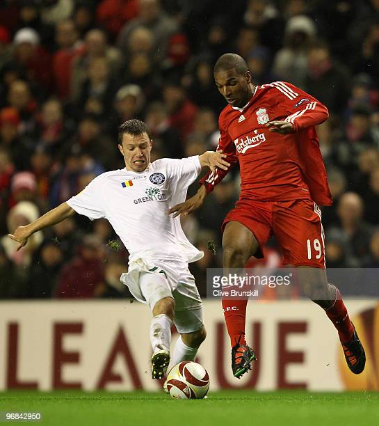 Ryan Babel of Liverpool holds off a challenge from Iulian Apostol of Unirea Urziceni during the UEFA Europa League Round 32 first leg match between...