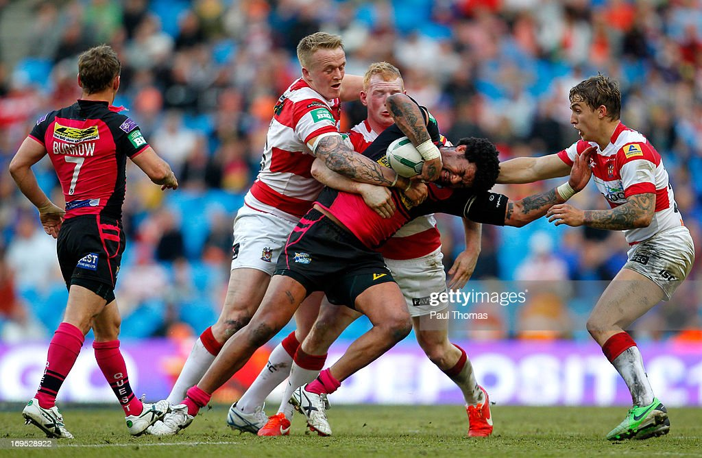 Ryan Bailey (C) of Leeds is tackled by Dominic Crosby (L), Liam Farrell and Sam Powell (R) of Wigan during the Super League Magic Weekend match between Leeds Rhinos and Wigan Warriors at the Etihad Stadium on May 26, 2013 in Manchester, England.