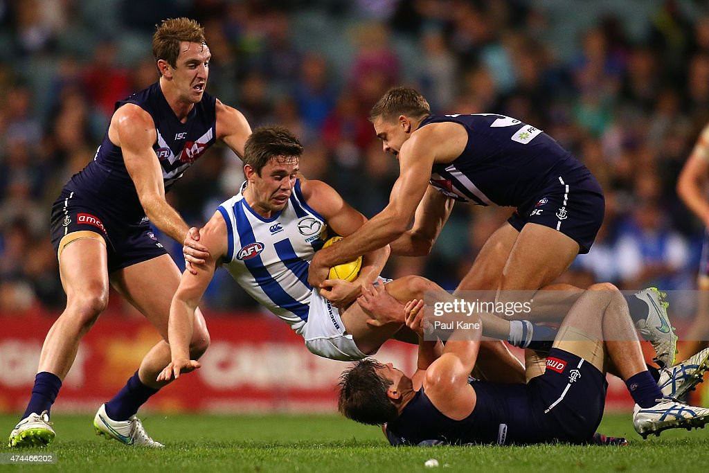 Ryan Bastinac of the Kangaroos gets tackled by Michael Barlow Stephen Hill and Nick Suban of the Dockers during the round eight AFL match between the...