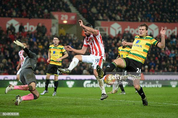 Ryan Bennett and Declan Rudd of Norwich City battle for the ball with Jonathan Walters of Stoke City during the Barclays Premier League match between...