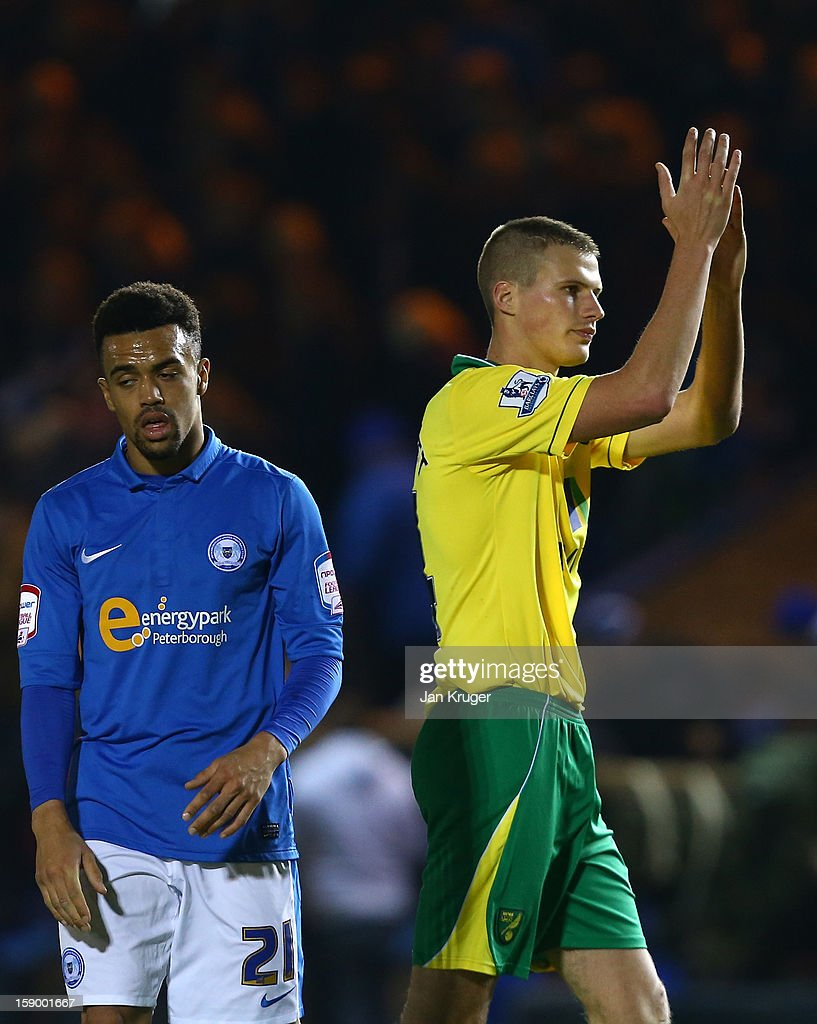 Ryan Bennett of Norwich City applauds the fans as Nicky Ajose of Peterborough United looks dejected during the FA Cup with Budweiser third round match between Peterborough United and Norwich City at London Road Stadium on January 5, 2013 in Peterborough, England.