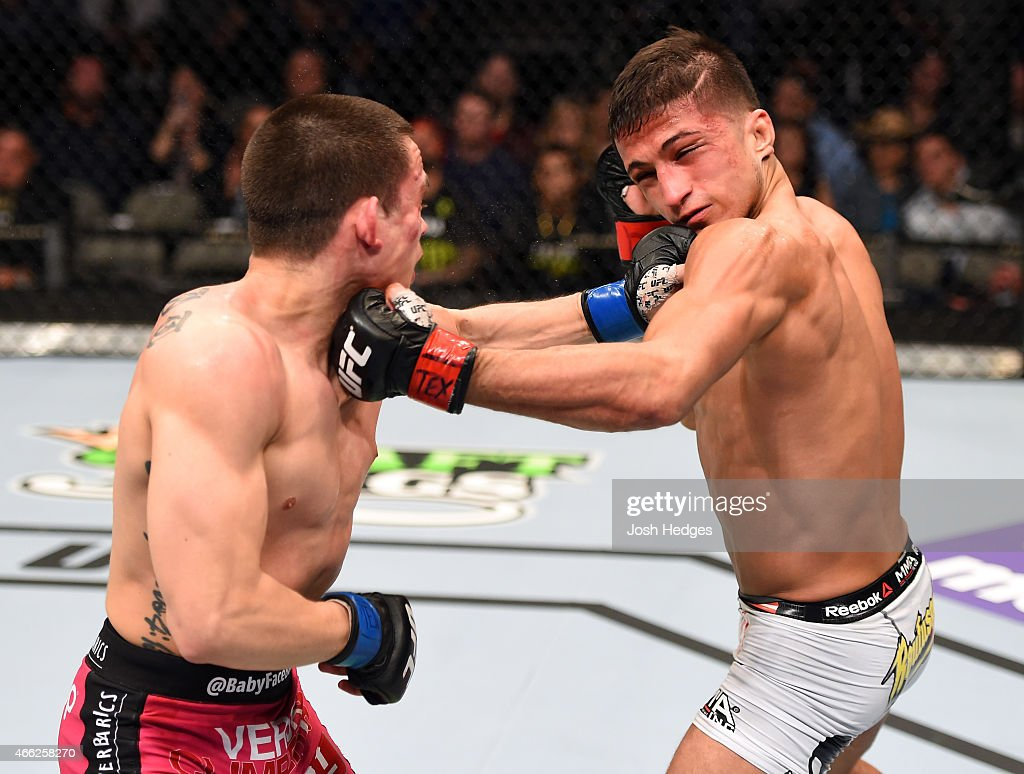 Ryan Benoit lands a punch to the chin of Sergio Pettis in their flyweight bout during the UFC 185 event at the American Airlines Center on March 14, 2015 in Dallas, Texas.