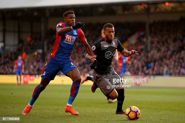 Ryan Bertrand of Southampton and Wilfried Zaha of Crystal Palace compete for the ball during the Premier League match between Crystal Palace and...