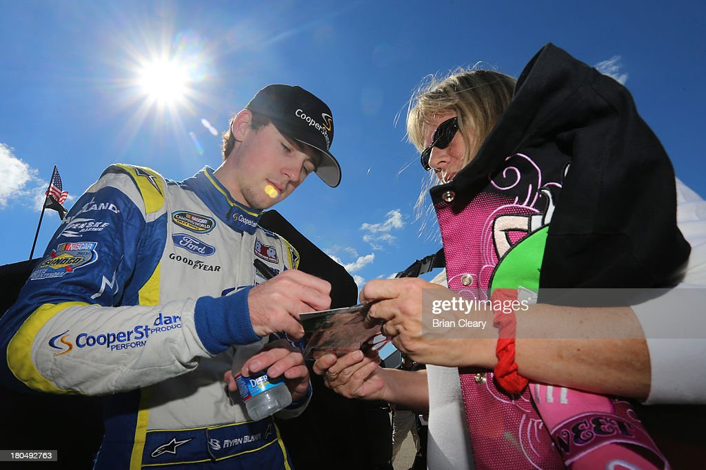 Ryan Blaney, driver of the #29 Cooper Standard Ford, signs autographs during practice for the NASCAR Camping World Truck Series enjoyillinois.com 225 at Chicagoland Speedway on September 13, 2013 in Joliet, Illinois.