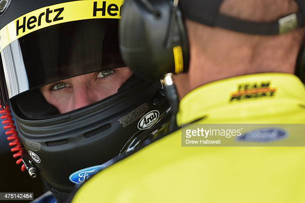 Ryan Blaney driver of the Hertz Ford talks with a crew member in the garage area during practice for the NASCAR XFINITY Series Buckle Up 200...