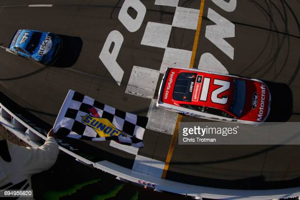 Ryan Blaney driver of the Motorcraft/Quick Lane Tire Auto Center Ford takes the checkered flag ahead of Kevin Harvick driver of the Busch Beer Ford...