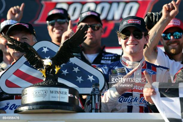 Ryan Blaney driver of the Motorcraft/Quick Lane Tire Auto Center Ford poses with the trophy in Victory Lane after winning the Monster Energy NASCAR...