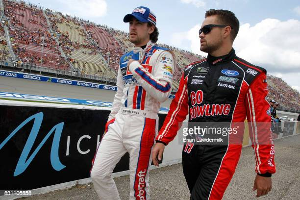 Ryan Blaney driver of the Motorcraft/SKF Ford talks to Ricky Stenhouse Jr driver of the Go Bowling Ford on the grid prior to the Monster Energy...