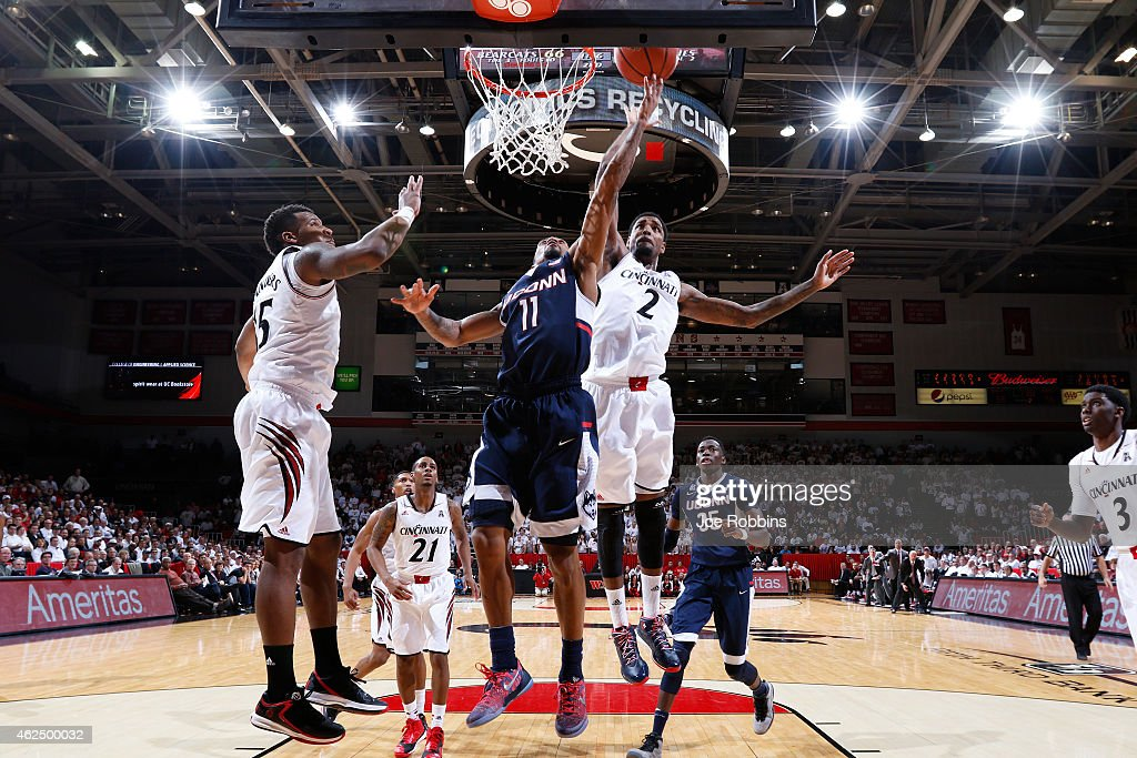 Ryan Boatright of the Connecticut Huskies drives to the basket against Octavius Ellis and Jermaine Sanders of the Cincinnati Bearcats during the game...
