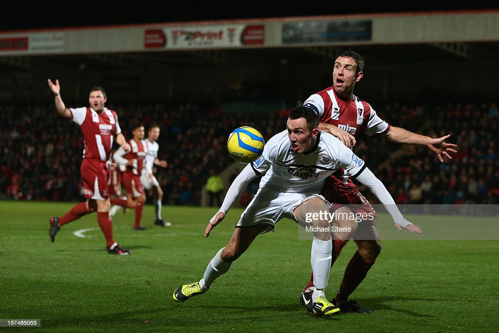 Ryan Bowman of Hereford United shields the ball as Billy Jones (R) of Cheltenham Town challenges during the FA Cup with Budweiser Second Round match between Cheltenham Town and Hereford United at the Abbey Business Stadium on December 3, 2012 in Cheltenham, England.