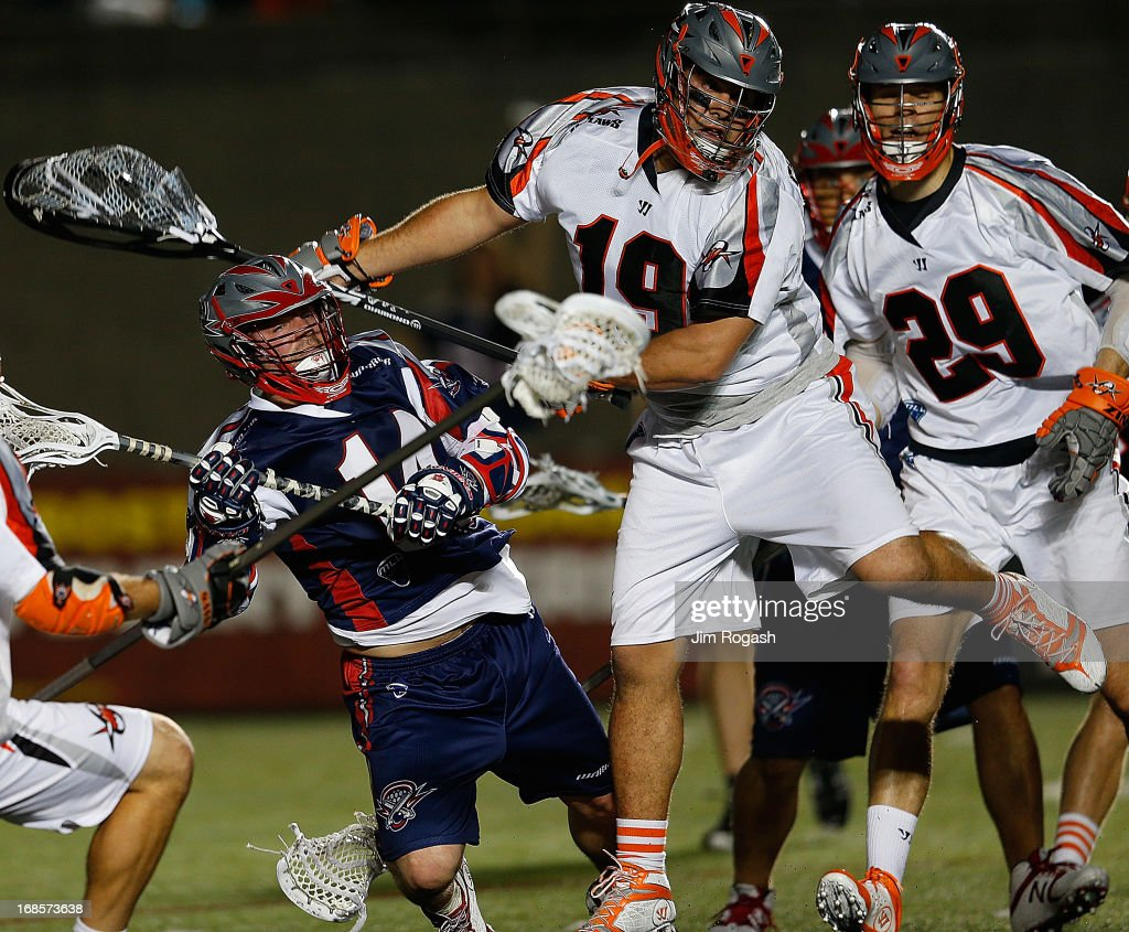 Ryan Boyle #14 of the Boston Cannons is knocked to the ground by goalie Jesse Schwartzman #19 of the Denver Outlaws in the second half at Harvard Stadium on May 11, 2013 in Boston, Massachusetts.