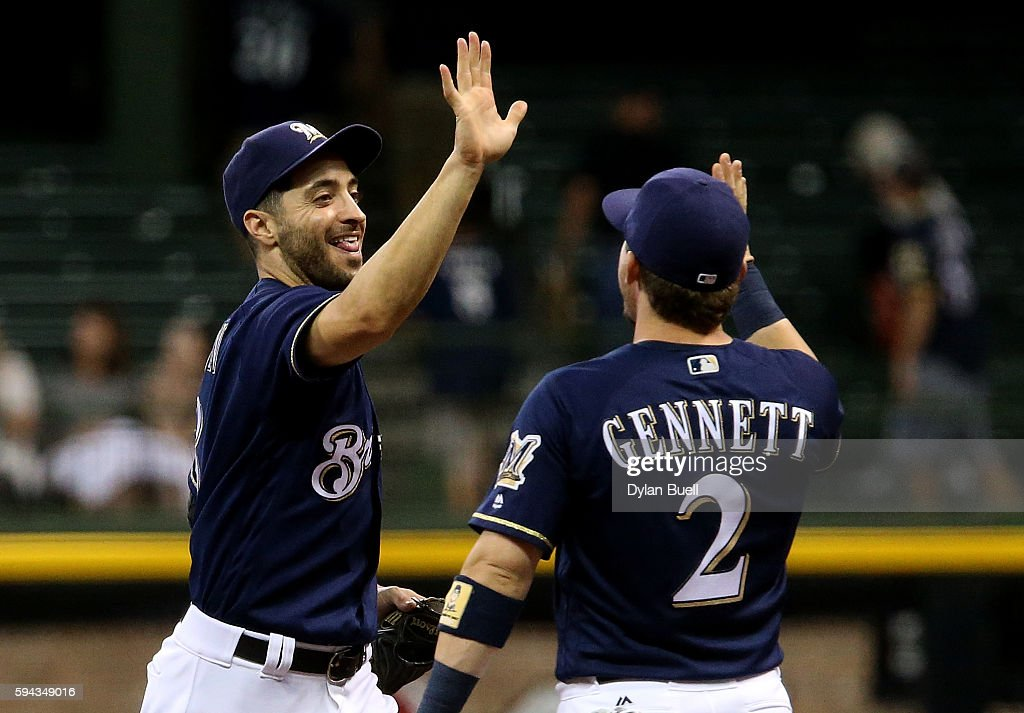 Ryan Braun #8 and Scooter Gennett #2 of the Milwaukee Brewers celebrate after beating the Colorado Rockies 4-2 at Miller Park on August 22, 2016 in Milwaukee, Wisconsin.