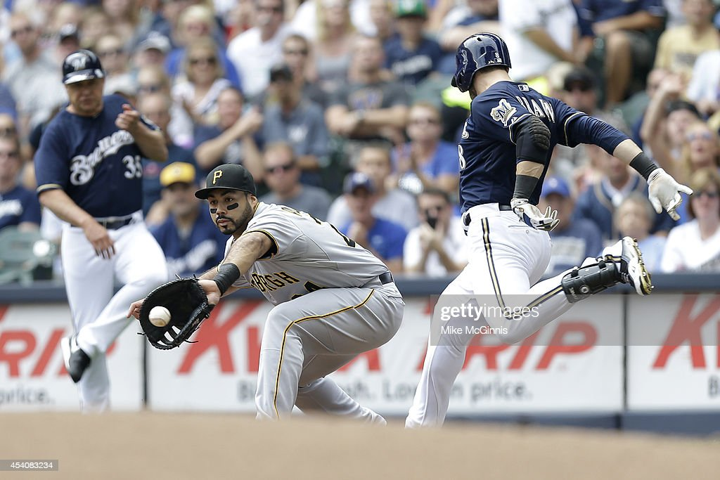 Ryan Braun #8 of the Milwaukee Brewers beats the throw to Pedro Alvarez #24 of the Pittsburgh Pirates at first base for a single during the bottom of the first inning at Miller Park on August 24, 2014 in Milwaukee, Wisconsin.
