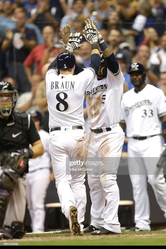 Ryan Braun of the Milwaukee Brewers celebrates with Jonathan Villar after reaching on a RBI triple hit by Hernan Perez during the seventh inning...