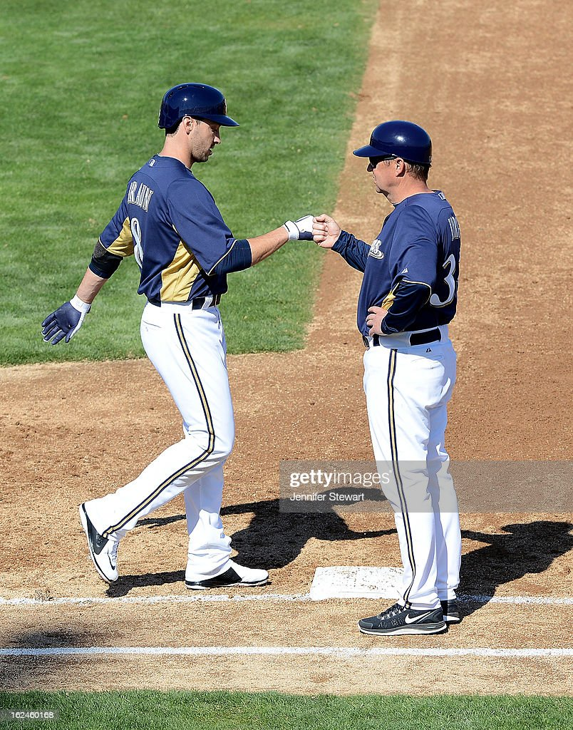 Ryan Braun #8 of the Milwaukee Brewers is congratulated by first base coach Garth Iorg #34 after bring walked in the spring training game against the Oakland Athletics at Maryvale Baseball Park on February 23, 2013 in Phoenix, Arizona.
