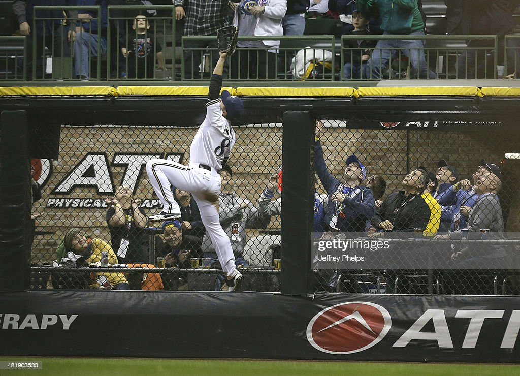 Ryan Braun #8 of the Milwaukee Brewers leaps up on the wall as he watches the two run home run of Atlanta Braves' Jason Heyward in the fifth inning of a game at Miller Park on April 1, 2014 in Milwaukee, Wisconsin.