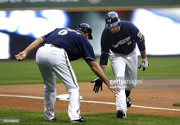 Ryan Braun of the Milwaukee Brewers rounds third base slapping hands with third base coach Ed Sedar after hitting a home run against the Philadelphia...