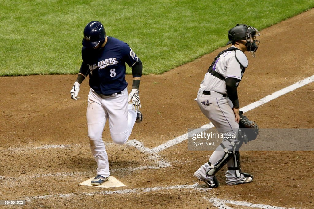 Ryan Braun #8 of the Milwaukee Brewers scores a run past Tony Wolters #14 of the Colorado Rockies in the sixth inning at Miller Park on April 4, 2017 in Milwaukee, Wisconsin.