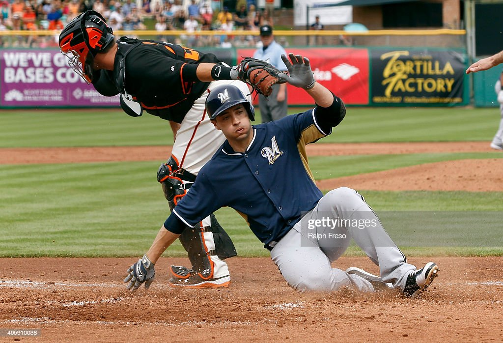 Ryan Braun of the Milwaukee Brewers slides across home plate to score a run as catcher Buster Posey of the San Francisco Giants applies a late tag...