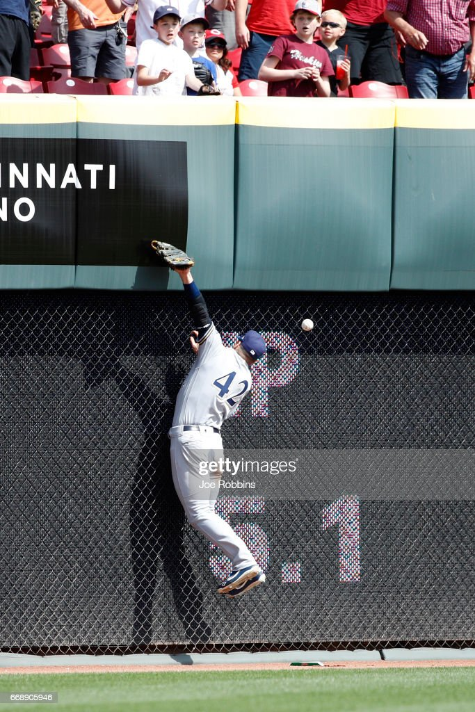 Ryan Braun #8 of the Milwaukee Brewers tries to catch a ball against the left field wall in the seventh inning of the game against the Cincinnati Reds at Great American Ball Park on April 15, 2017 in Cincinnati, Ohio. The Reds defeated the Brewers 7-5. All players are wearing #42 in honor of Jackie Robinson Day.