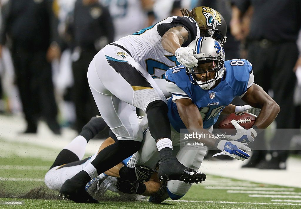 Ryan Broyles #84 of the Detroit Lions is tackled by Jamell Fleming #29 of the Jacksonville Jaguars in the fourth quarter during a preseason game at Ford Field on August 22, 2014 in Detroit, Michigan.