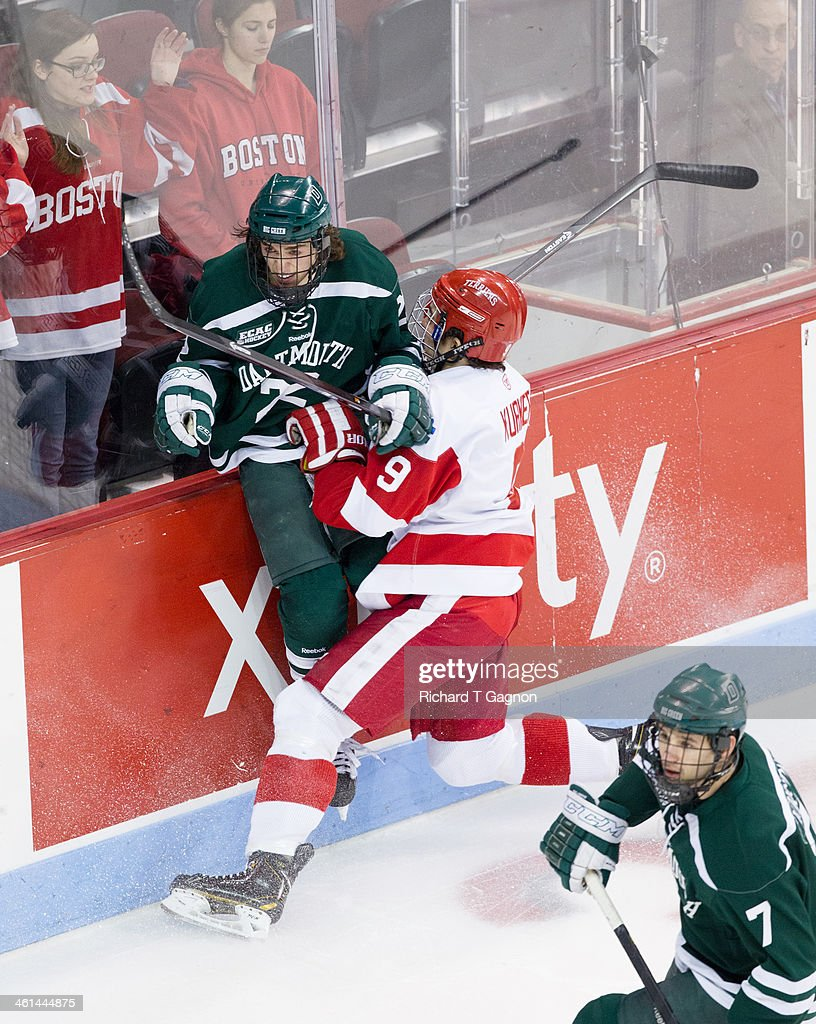 Ryan Bullock #22 of the Dartmouth College Big Green gets checked by Sam Kurker #9 of the Boston University Terriers during NCAA hockey action at Agganis Arena on January 8, 2014 in Boston, Massachusetts.