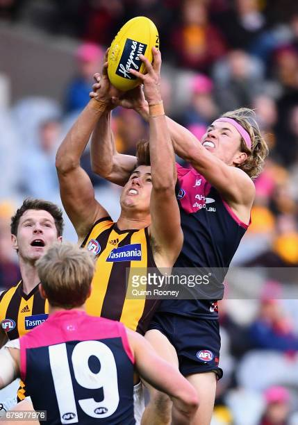 Ryan Burton of the Hawks and Jayden Hunt of the Demons compete for a mark during the round seven AFL match between the Melbourne Demons and the...