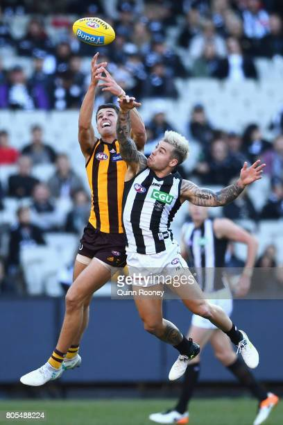 Ryan Burton of the Hawks marks over the top of Jamie Elliott of the Magpies during the round 15 AFL match between the Hawthorn Hawks and the...