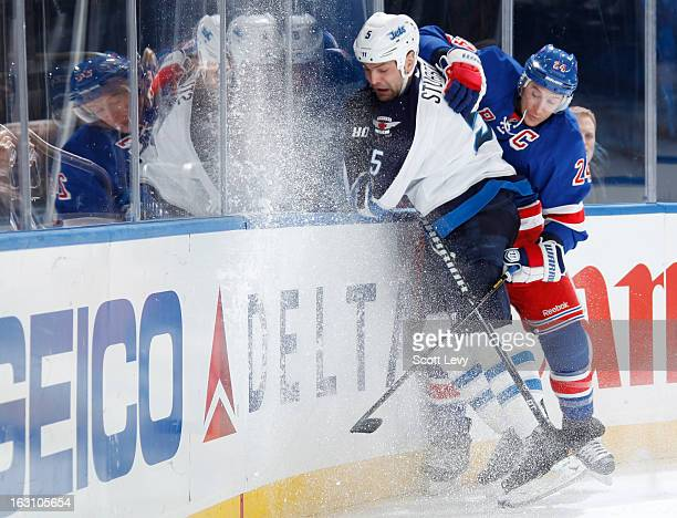 Ryan Callahan of the New York Rangers checks Mark Stuart of the Winnipeg Jets at Madison Square Garden on February 26 2013 in New York City