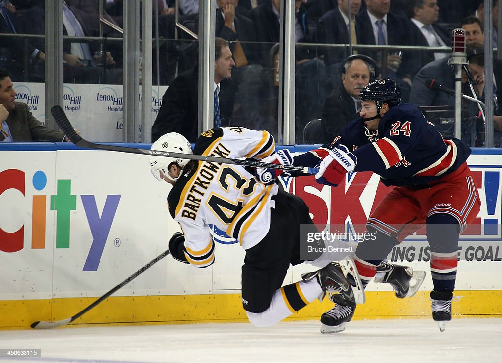 Ryan Callahan #24 of the New York Rangers checks Matt Bartkowski #43 of the Boston Bruins into the boards during the second period at Madison Square Garden on November 19, 2013 in New York City.