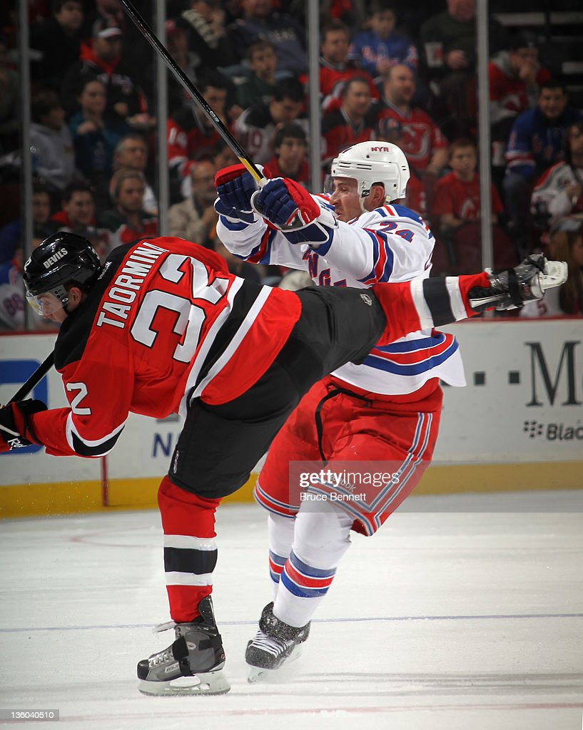 <a gi-track='captionPersonalityLinkClicked' href=/galleries/search?phrase=Ryan+Callahan&family=editorial&specificpeople=809690 ng-click='$event.stopPropagation()'>Ryan Callahan</a> #24 of the New York Rangers hits Matt Taormina #32 of the New Jersey Devils at the Prudential Center on December 20, 2011 in Newark, New Jersey.