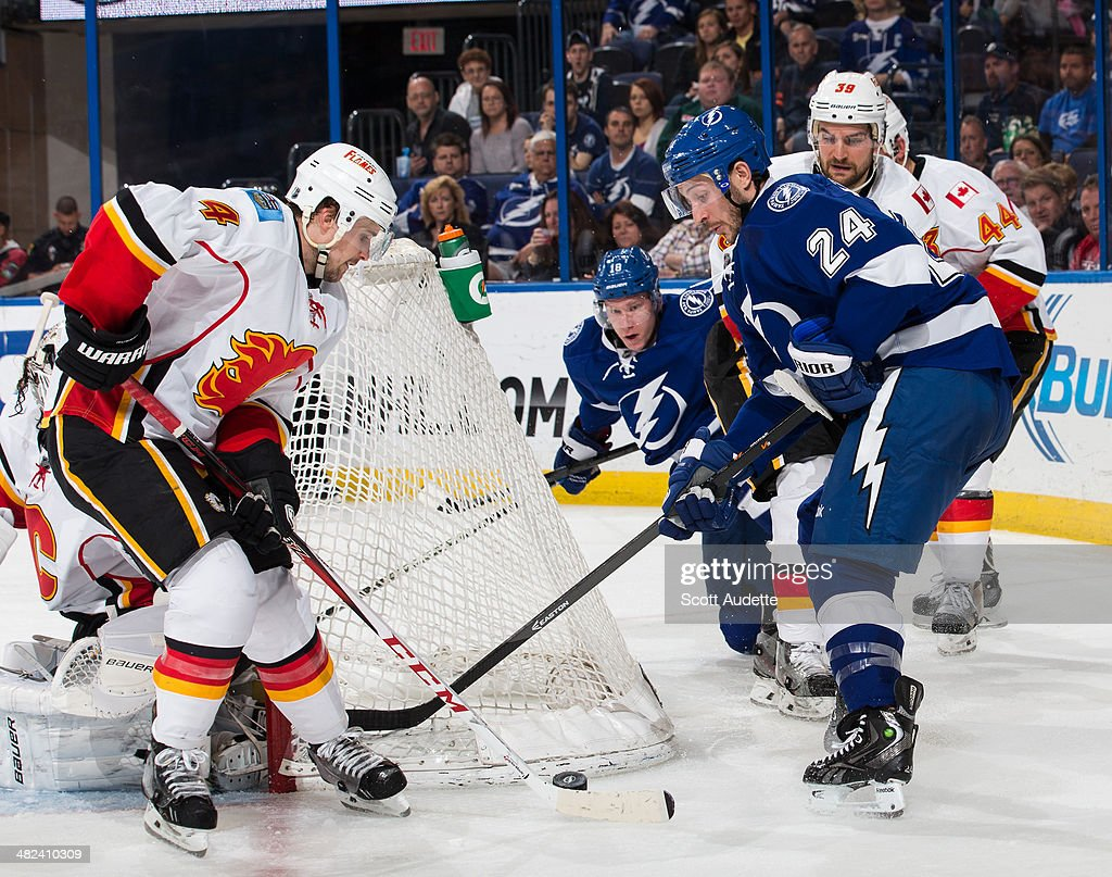<a gi-track='captionPersonalityLinkClicked' href=/galleries/search?phrase=Ryan+Callahan&family=editorial&specificpeople=809690 ng-click='$event.stopPropagation()'>Ryan Callahan</a> #24 of the Tampa Bay Lightning battles for the puck against <a gi-track='captionPersonalityLinkClicked' href=/galleries/search?phrase=Kris+Russell&family=editorial&specificpeople=879805 ng-click='$event.stopPropagation()'>Kris Russell</a> #4 of the Calgary Flames during the third period at the Tampa Bay Times Forum on April 3, 2014 in Tampa, Florida.